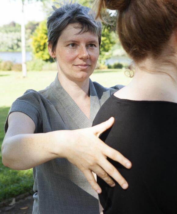 Frau stehend berührt Klientin am Rücken, Aufrichtung des Körpers