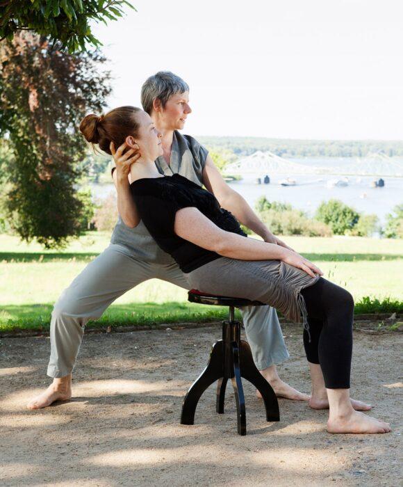 Frau auf Stuhl nach hinten lehnend,Körpergefühl wahrnehmend