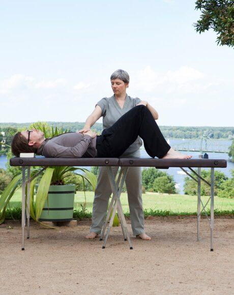 Mann liegend mit aufgestellten Beinen, Aufrichtung der Wirbelsäule